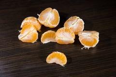 Lobules of mandarin on dark wooden table. Lobules of mandarin on the dark wooden table stock image