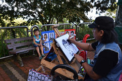 Local artist draws a quick sketch of children on top of Penang H Royalty Free Stock Photos