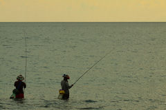 Local Asia mans fishing in the sea with fair sun light early morning at sunrise time. Local Asia mans fishing with self made fishing rob in the sea. Next to Royalty Free Stock Photo