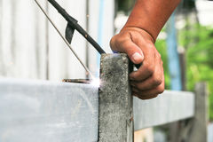 Local Asian technical worker welding steel iron on a concrete ro Stock Photo