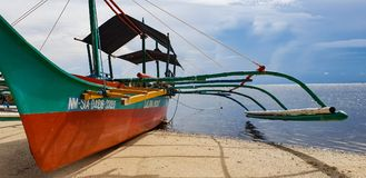 A commercial banka boat awaits tourists on the beach of Siargao ISland in the Philippines. A local Banka boat awaits tourists on the beach of Siargao Island in stock photos