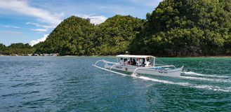 Banka boat ferries tourists to Sugba Lagoon on the island of Siargao in the Philippines stock images