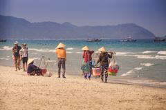 Local Beach Vendors in Round Hats Try to Sell Food to Tourists. NHA TRANG/VIETNAM - APRIL 16 2017: Local beach vendors in Vietnamese national hats with baskets Royalty Free Stock Photo