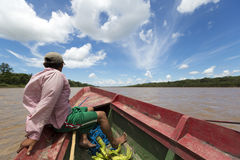 Local Bolivian man traveling on a wooden boat on Beni river,  Ru. Indigenous Bolivian man traveling on a wooden boat on Beni river in Bolivian jungle near Stock Image