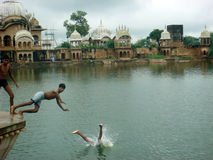 Local boys jumping in the pond. Teenage boys jumping in the pond at Vrindavan to enjoy swim stock photography