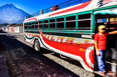 Local bus & Agua volcano, Antigua, Guatemala. Antigua, Guatemala - Oct 5, 2014: Typical bus known locally as a camioneta in Spanish colonial town of Antigua stock image