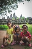 Local Cambodian children posing to the camera in front of Angkor Wat royalty free stock images