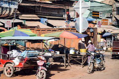 Local Cambodian street scene. Showing boys climbing and playing on a large rubbish bin Stock Image