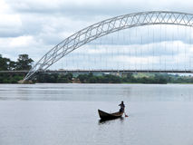 Local Canoe on Ghana's Volta River. An African paddler in a local canoe on the Volta River in Ghana, West Africa, with the suspension bridge at Atimpoku in the Stock Image