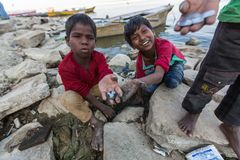 Local children dig in the sand on the banks of the Holy Ganges river to find coins thrown as a gift to the gods by pilgrims. VARANASI, INDIA - MAR 13, 2018 royalty free stock photography