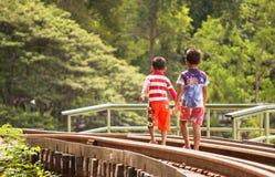 Local children walking on the railway in Kanchanaburi Stock Photos
