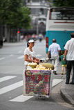 Local Chinese. A local Chinese woman hawker in Shanghai city.  Using the most basic tools as her mobile store, her stock includes fresh fruits sold on a wooden Royalty Free Stock Photos