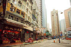 Local chinese shops and people walking on streets with tall concrete buildings in asian city Stock Photos