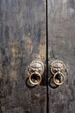 Local chinese wooden door as background. Metal chinese door knockers with weathered wooden doors Stock Photos