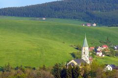 Local church in Oberwiesenthal, Germany. Erzgebirge mountains in May; fresh green fields rising up the hill, edge of town and a local church in a valley. Resort Stock Photography