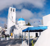 Local church in Oia village in Santorini, Greece. Decorated with flags for local festival, panoramic image Royalty Free Stock Photo