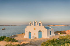 Local church in Pirgaki in Paros island against the blue Aegean sea. A beautiful landscape. Royalty Free Stock Image