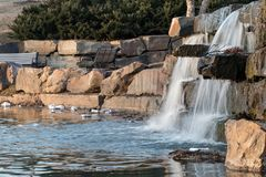 Tulsa, Oklahoma - February 17, 2018. Shameful litter and debris pollutes a water pond in a city park. This local city park has unsightly litter polluting its Royalty Free Stock Photo