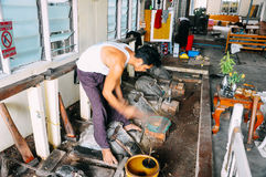 Local craftsman making gold leaf in Mandalay. Royalty Free Stock Images