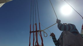 Local crew member tying ropes on felucca boat stock video