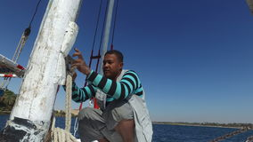 Local crew member tying ropes on felucca boat stock footage