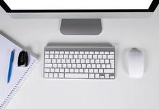 Local de trabalho com computador e chaves sem fio do teclado e do rato, do caderno e do carro no fundo branco Imagem de Stock Royalty Free
