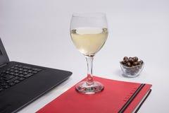 Local de trabalho com laptop preto, caderno, bolas do chocolate e vinho branco de vidro no fundo branco Fotografia de Stock Royalty Free