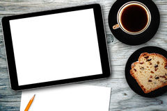 Local de trabalho com o copo digital da tabuleta, do caderno, do bolo e de café Foto de Stock Royalty Free