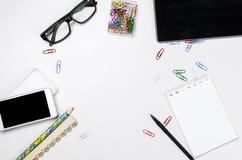 Local de trabalho com tabuleta, smartphone, pena, bloco de notas e vidros Fotografia de Stock Royalty Free