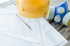 Local de trabalho da engenharia, desenhos, capacete protetor da construção e opinião do respirador da poeira da parte superior Fotos de Stock