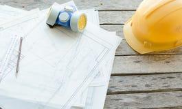Local de trabalho da engenharia, desenhos, capacete protetor da construção e opinião do respirador da poeira da parte superior Imagem de Stock Royalty Free