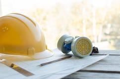 Local de trabalho da engenharia, desenhos, capacete protetor da construção e respirador da poeira Foto de Stock Royalty Free
