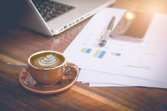 Local de trabalho da manhã: xícara de café com objetos da arte e do negócio do latte Imagens de Stock