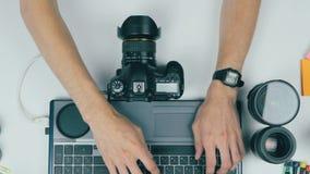Local de trabalho de cima de Fotógrafo irreconhecível que conecta sua câmera ao portátil vídeos de arquivo