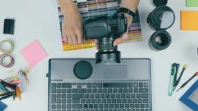 Local de trabalho de cima de Fotógrafo irreconhecível que trabalha com sua bateria em mudança da câmera vídeos de arquivo