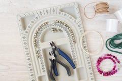 Local de trabalho do desenhista da joia Feito a mão, conceito do ofício Materiais para fazer a joia Perlando ajustes dos bracelet fotos de stock royalty free