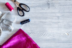 Local de trabalho do desenhista da roupa tela fita, linha e sciccors de medição no copyspace de madeira claro da opinião superior imagem de stock
