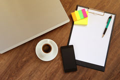 Local de trabalho do escritório com portátil, o telefone esperto e o copo de café na tabela de madeira Foto de Stock Royalty Free