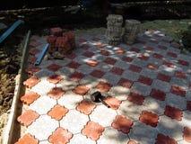 Local de trabalho dos trabalhadores que colocam pedras de pavimentação decorativas foto de stock