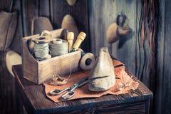 Local de trabalho pequeno do sapateiro com ferramentas, sapatas e laços Fotografia de Stock Royalty Free