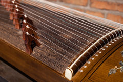 Local details of  Guzheng. The guzheng or gu zheng (Chinese: 古箏), also simply called zheng (箏, gu 古 means ancient), is a Chinese plucked zither. It has Royalty Free Stock Photography