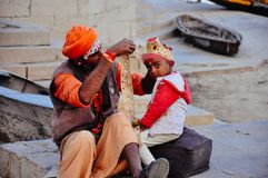 A local dresses a youth in Varanasi, India. A local dresses a youth for a celebration in Varanasi, India royalty free stock photo