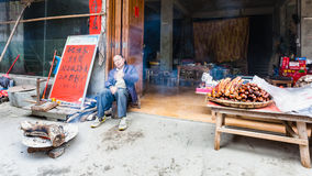 Local eatery and smokehouse in Chengyang. CHENGYANG, CHINA - MARCH 27, 2017: seller near local eatery and smokehouse in Chengyang village of Sanjiang Dong Royalty Free Stock Photography