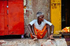 A local sits in the shade in Varanasi, India. A local elder sits in the shade in Varanasi, India stock photos