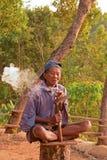 A local elderly worker smoking cigarette on chopped tree trunk at Punthuk Setumbu Hills