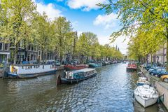 Local et touriste marchant sur le canal de Keizersgracht au printemps dans la région de Jordaan avec des bateaux, des vélos et de Photo stock