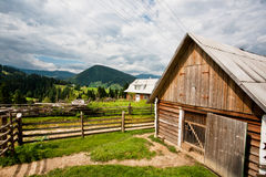 Local farm past the green mountain forests Stock Images