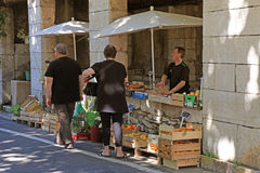 Local farmer market in Saint Paul de Vence, Provence, France. SAINT-PAUL-DE-VENCE, FRANCE - MAY 12, 2013: People buy fruit and vegetables at local farmer market Royalty Free Stock Image