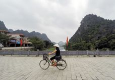 Local female vietnamese with traditional hat, riding a bike at Hoa Lu Temple bridge, lake surrounded by limestones - April 4th, 20 Royalty Free Stock Photo