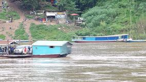 Local ferry boat carry people and vehicles across river. Luang prabang, Laos - AUGUST 8, 2015: Local ferry boat carry people and vehicles across Mekong river stock footage